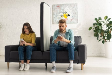 Photo for Young couple using smartphones near huge model of smartphone on couch - Royalty Free Image