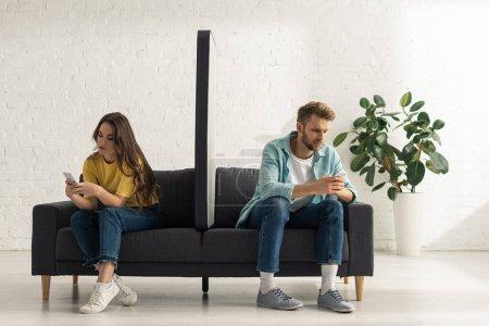 Photo pour Modèle de smartphone sur canapé entre jeunes couples utilisant des smartphones dans le salon - image libre de droit