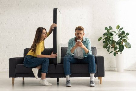 Photo for Young woman holding model of smartphone while boyfriend chatting on couch - Royalty Free Image