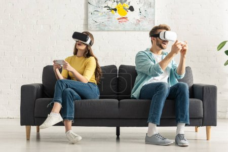 Photo for Couple using virtual reality headsets and smartphones on couch - Royalty Free Image