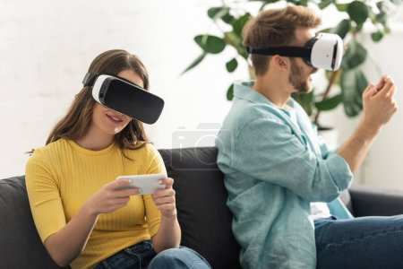 Photo for Selective focus of smiling girl in vr headset using smartphone near boyfriend on sofa in living room - Royalty Free Image