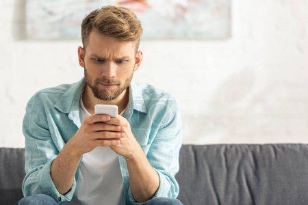 Verwirrter Mann schaut zu Hause auf Sofa auf Smartphone