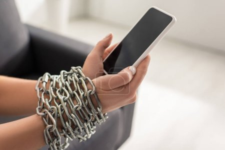 Cropped view of woman with metal chain around hands holding smartphone with blank screen on couch