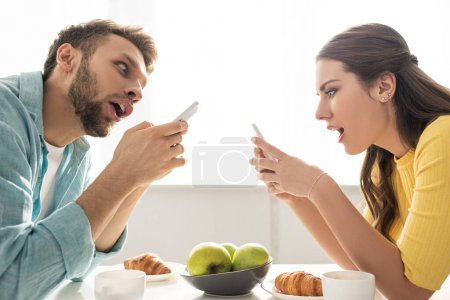 Photo for Side view of shocked couple using smartphones near breakfast on table - Royalty Free Image