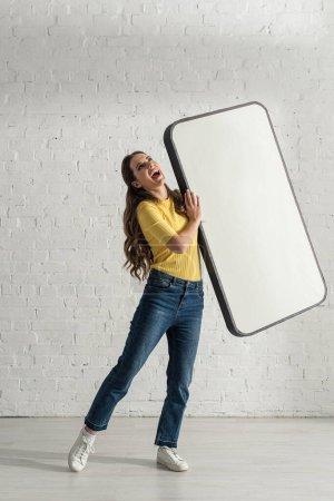 Photo pour Belle femme riante tenant un modèle de téléphone intelligent à la maison - image libre de droit
