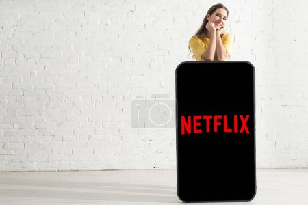 KYIV, UKRAINE - FEBRUARY 21, 2020: Smiling girl looking at camera near big model of smartphone with netflix app at home