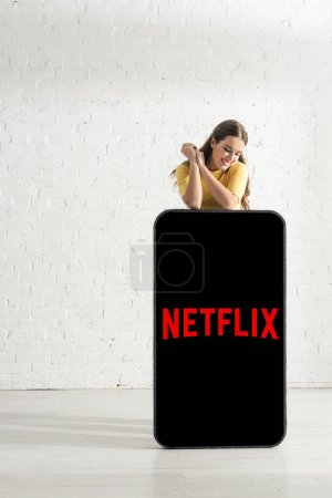 KYIV, UKRAINE - FEBRUARY 21, 2020: Attractive girl smiling near model of smartphone with netflix app