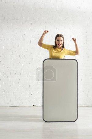 Photo pour Femme heureuse montrant geste oui près de grand modèle de smartphone à la maison - image libre de droit
