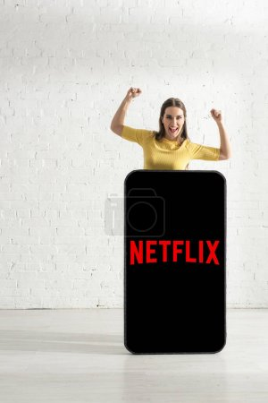 KYIV, UKRAINE - FEBRUARY 21, 2020: Positive woman showing yes gesture near netflix app on model of smartphone