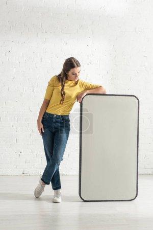 Attrayant fille à la recherche de grand modèle de smartphone près de mur de briques blanches