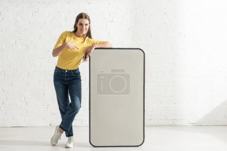 Photo pour Femme souriante pointant du doigt le modèle du smartphone - image libre de droit
