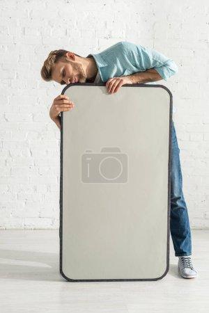 Foto de Un hombre guapo besando modelo enorme de teléfono inteligente cerca de la pared de ladrillo blanco. - Imagen libre de derechos