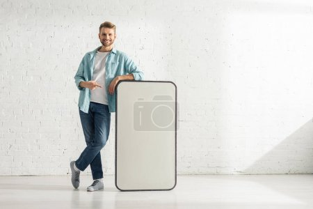 Handsome man smiling at camera and pointing with finger at big model of smartphone at home