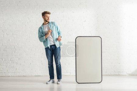 Foto de Hombre temeroso mirando el gran modelo de teléfono inteligente cerca de la pared de ladrillo blanco. - Imagen libre de derechos