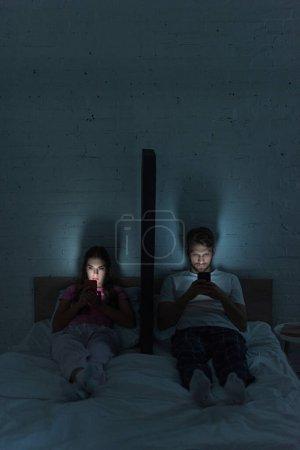Photo pour Jeune couple avec smartphones assis près du modèle de smartphone sur le lit la nuit - image libre de droit