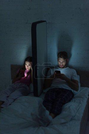 Photo pour Couple utilisant des smartphones près du modèle de smartphone sur le lit la nuit - image libre de droit