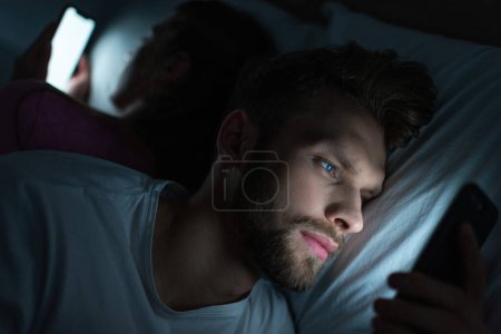Photo for Selective focus of handsome man using smartphone near girlfriend on bed at night - Royalty Free Image