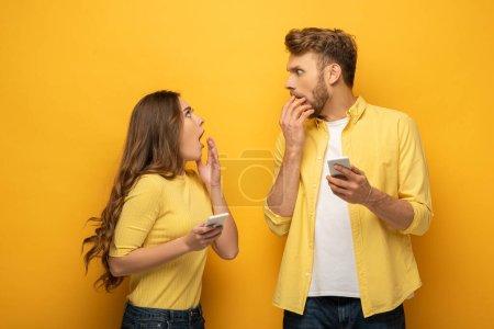 Photo pour Couple surpris avec smartphones se regardant sur fond jaune - image libre de droit
