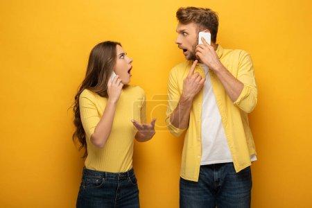 Photo pour Couple choqué se regardant tout en parlant sur les smartphones sur fond jaune - image libre de droit