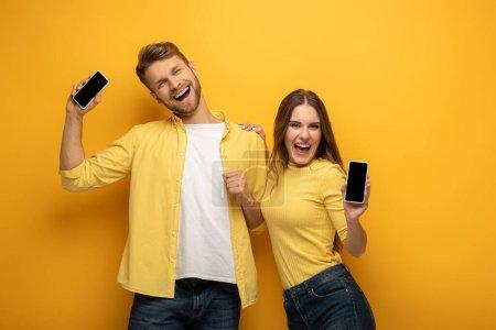 Photo pour Joyeux jeune couple montrant des smartphones et regardant la caméra sur fond jaune - image libre de droit