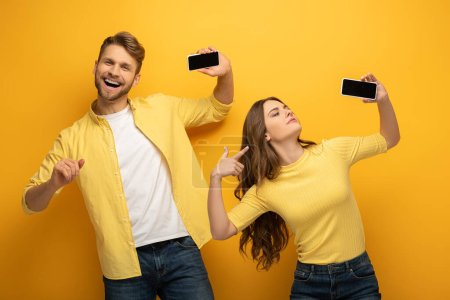 Photo for Positive couple showing smartphones with blank screens on yellow background - Royalty Free Image