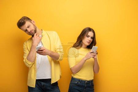 Photo pour Couple pensif utilisant des smartphones sur fond jaune - image libre de droit