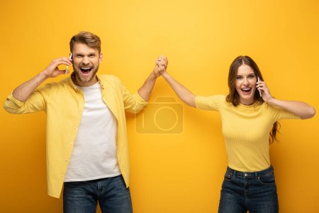 Photo for Happy couple high five while talking on smartphones on yellow background - Royalty Free Image