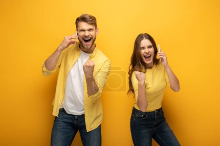 Photo pour Couple joyeux montrant geste oui tout en parlant sur les smartphones sur fond jaune - image libre de droit