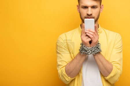 Handsome man with metal chain around hands holding smartphone on yellow background