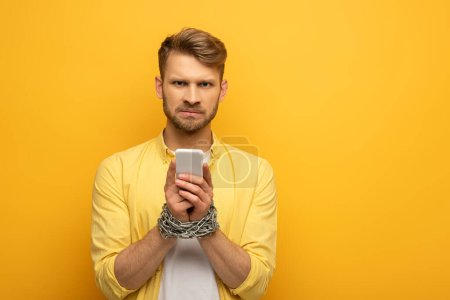 Photo for Sad man with tied hands with metal chain holding smartphone on yellow background - Royalty Free Image