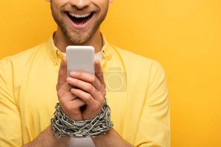 Photo pour Vue recadrée de l'homme heureux avec chaîne autour des mains tenant smartphone sur fond jaune - image libre de droit