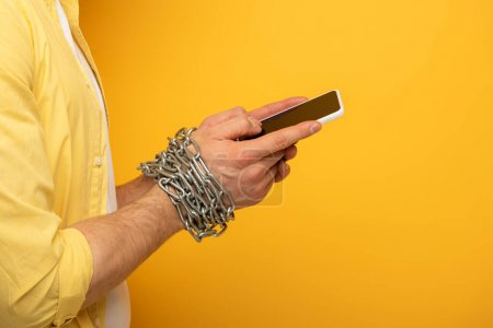 Cropped view of man with metal chain around hands holding smartphone with blank screen on yellow background