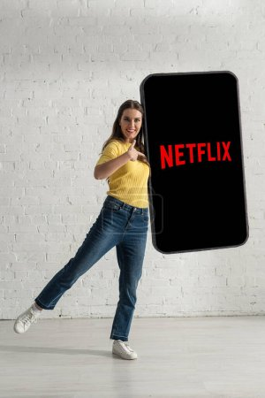 KYIV, UKRAINE - FEBRUARY 21, 2020: Smiling girl pointing with finger at model of smartphone with netflix app near white brick wall
