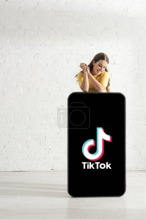 KYIV, UKRAINE - FEBRUARY 21, 2020: Smiling woman looking at big model of smartphone with TikTok app near white brick wall