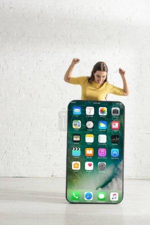 Photo pour KYIV, UKRAINE - 21 FÉVRIER 2020 : Fille positive regardant grand modèle de smartphone avec écran d'iphone tout en montrant geste ouais - image libre de droit