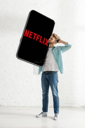 Photo pour KIEV, UKRAINE - FEBRUARY 21, 2020 : Thoughtful man with hand near head holding big model of smartphone with netflix app - image libre de droit