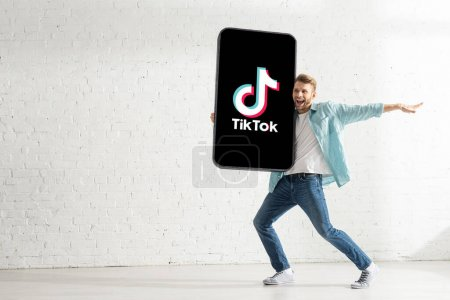 KYIV, UKRAINE - FEBRUARY 21, 2020: Handsome man smiling while holding big model of smartphone with TikTok app at home