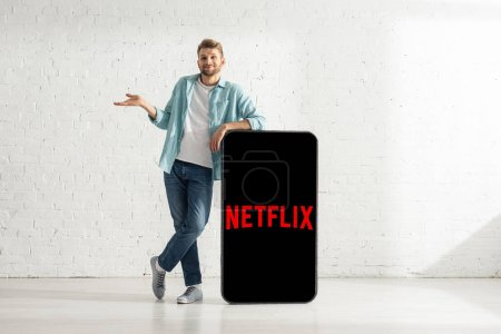 KYIV, UKRAINE - FEBRUARY 21, 2020: Smiling man showing shrug gesture near model of smartphone with netflix app
