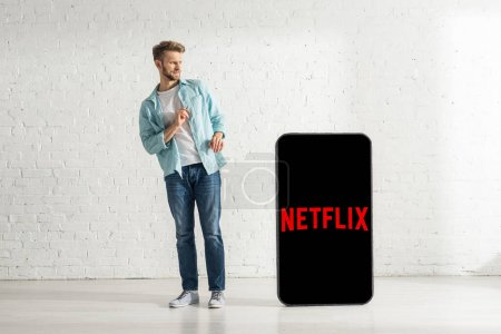 KYIV, UKRAINE - FEBRUARY 21, 2020: Scared man standing near huge model of smartphone with netflix app
