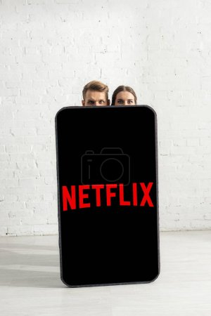 Photo pour KIEV, UKRAINE - 21 FEVRIER 2020 : Couple looking at camera near huge model of smartphone with netflix app at home - image libre de droit