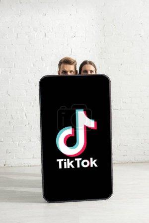 Foto de KYIV, UCRANIA - 21 de febrero de 2020: Pareja joven mirando la cámara cerca de un enorme modelo de teléfono inteligente con la aplicación TikTok - Imagen libre de derechos