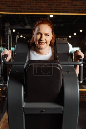 Photo for Purposeful overweight girl doing arms extension exercise on fitness machine - Royalty Free Image