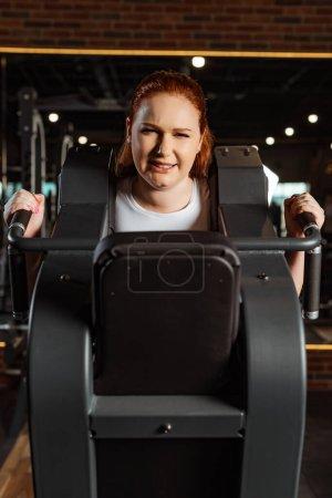 Foto de Una chica con sobrepeso que hace ejercicio de extensión de armas en máquinas de fitness. - Imagen libre de derechos