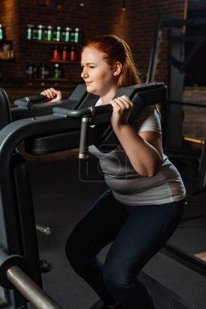 Photo pour Une jeune fille en surpoids fait un exercice d'extension sur une machine de conditionnement physique - image libre de droit