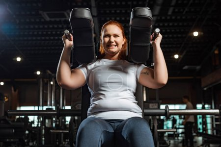 Photo for Cropped view of purposeful overweight girl doing arms extension exercise on fitness machine - Royalty Free Image