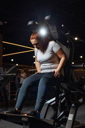 Photo pour Fille en surpoids dans la formation de vêtements de sport sur la machine de fitness dans la salle de gym - image libre de droit