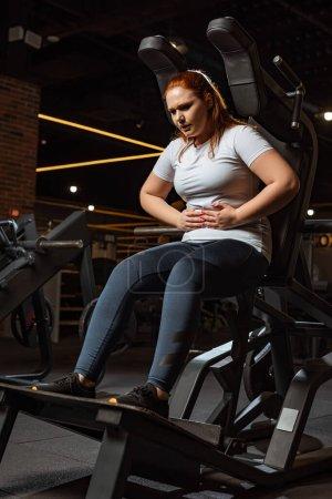 Photo pour Fatigué fille en surpoids toucher le ventre tout en étant assis sur la machine d'entraînement - image libre de droit