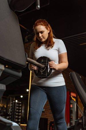 Photo pour Jolie fille en surpoids prenant le disque de poids de la machine de fitness - image libre de droit