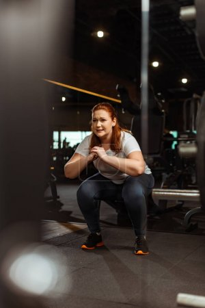 Photo pour Focus sélectif of overweight girl squatting with clenched hands in gym - image libre de droit