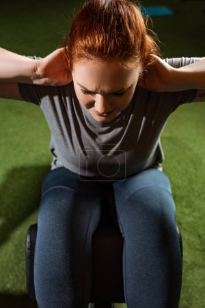 Photo for Overhead view of purposeful overweight girl doing abs exercise on fitness machine - Royalty Free Image